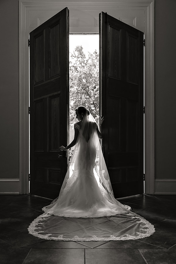 Bride opening church doors full length